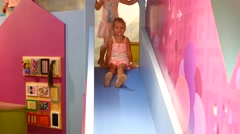 Kids sliding down on slide in indoors playground for children Stock Footage