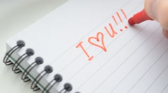 Writing I LOVE YOU U with red marker in notepad Stock Footage