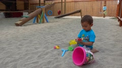 Boy plays in sand with toys Stock Footage