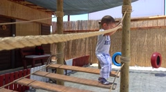 Boy jumps and walks on rope ladder Stock Footage