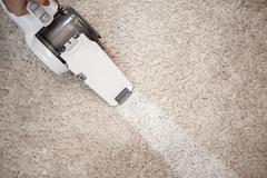 Top view of cordless handheld vacuum cleaner on beige carpet Stock Photos