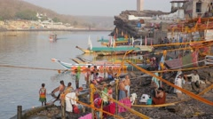Pilgrims bathing on ghats in Narmada river,Omkareshwar,India Stock Footage