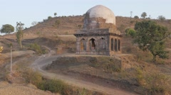 Small tomb in the hills with people on road,Mandu,India Stock Footage