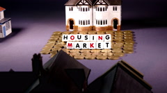 Model houses and pound coins. UK housing market concept. Stock Footage