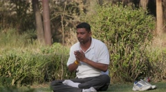 Man doing yoga exercise in Lal Bagh park,Indore,India Stock Footage