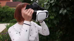 Young redhead woman using VR-helmet for smart phones. Augmented reality Stock Footage