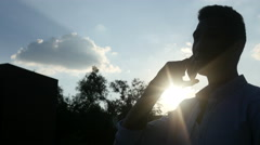 Black Man Talking on Phone, in front of Sun during Sunset, Silhouette Stock Footage