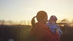 Young beautiful mother hugging her little son with nipple during sunset in Stock Footage