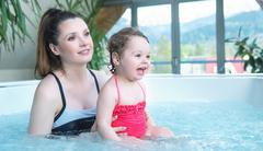 Mother and baby relaxing in a small swimming pool Kuvituskuvat