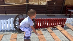 Child learns balance on rope ladder Stock Footage