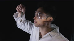 4K Scientist looking at chemical with scenes of war projected onto his face Stock Footage
