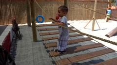 Child walks and jumps on rope ladder Stock Footage