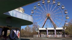 An abandoned and graffiti covered ferris wheel at an amusement park presents a Stock Footage