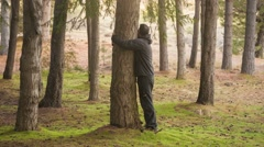 Man hugging a tree trunk in the woods Stock Footage