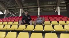 Sports fan awakened friend in stadium Stock Footage