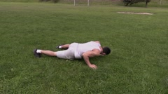 Young athlete doing push ups on grass in stadium Stock Footage