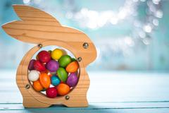 Easter concept with colorful handmade eggs and rabbit on wooden table Stock Photos