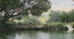 Teenage girl rope swing into local pond DCI 4K Stock Footage
