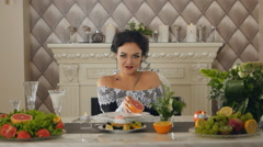 A woman sitting at a table posing with a grapefruit in the hands of Stock Footage