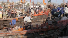 Fishermen unloading fish from boat,Veraval,India Stock Footage