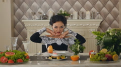 Brunette lady model at a table with fruits posing on camera Stock Footage