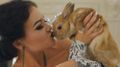 Girl holding and kissing rabbit Stock Footage
