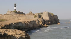 Rocky coast with fort,lighthouse and boat,Diu,India Stock Footage
