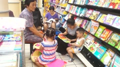 The mother took the children to read in the bookstore Stock Footage
