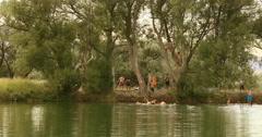 Teenager fun swimming rope swing local pond DCI 4K Stock Footage