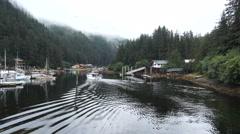 Fishing boat motors slowly to dock in Elfin Cove AK Stock Footage