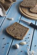 Slices of rye bread with sesame seeds, and garlic on blue wooden table. Stock Photos
