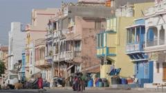 Women walking along colorful houses along street,Diu,India Stock Footage