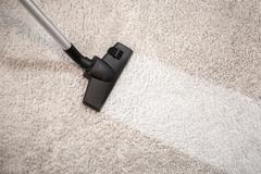 Vacuum cleaner vacuuming dusty carpet Stock Photos