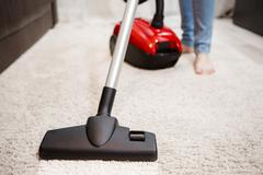 Woman doing cleaning in room, vacuuming white carpet. Image of female foot, red Stock Photos