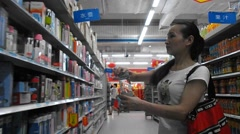 A young woman in a shopping mall to buy water bottles Stock Footage