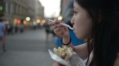 Korean woman tourist eating Doner Kebab at the night street Krakow - close up Stock Footage