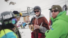 Snowboarders stay in helmet, sunglasses in encamp on ski resort. Eating banana Stock Footage