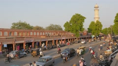 Traffic through bazaar and Ishwar Lat Tower,Jaipur,India Stock Footage