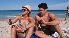 Good looking couple/friends sitting at the beach talking and smiling Stock Footage