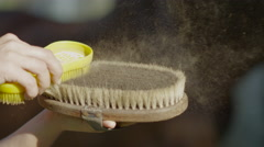 SLOW MOTION CLOSE UP: Cleaning dusty horse brushes after brushing a horse Stock Footage
