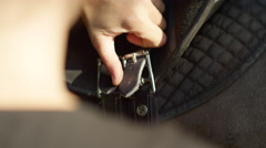 SLOW MOTION CLOSE UP: Unrecognizable person tightening a saddle on horse's back Stock Footage