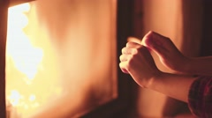 Woman Rubbing Hands in front of Burning Fireplace, 4K Close Up. Stock Footage
