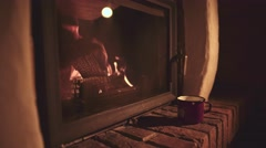 Man Hand taking Cup of Hot Drink, Relaxing Near the Burning Fireplace, 4K. Stock Footage