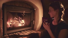 Woman sitting by the Cozy Fireplace with a Cup of Hot Drink , 4K. Stock Footage