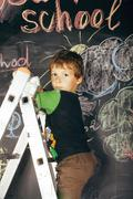 Little cute real boy at blackboard in classroom, back to school close up Stock Photos