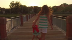 Mother and daughter walking on the pier at sunset Stock Footage