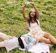 Two young pretty teenager girls best friends laying on grass making selfie photo Stock Photos