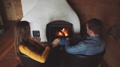 Young Couple sitting by the Cozy Fireplace, relaxing by the fire, 4K Stock Footage