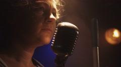 Scrubwoman scream in vintage microphone on stage of club. Smoke. Spotlight Stock Footage
