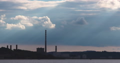 Shafts of sunlight fall on industrial chimneys in harbour 4K 60fps Stock Footage